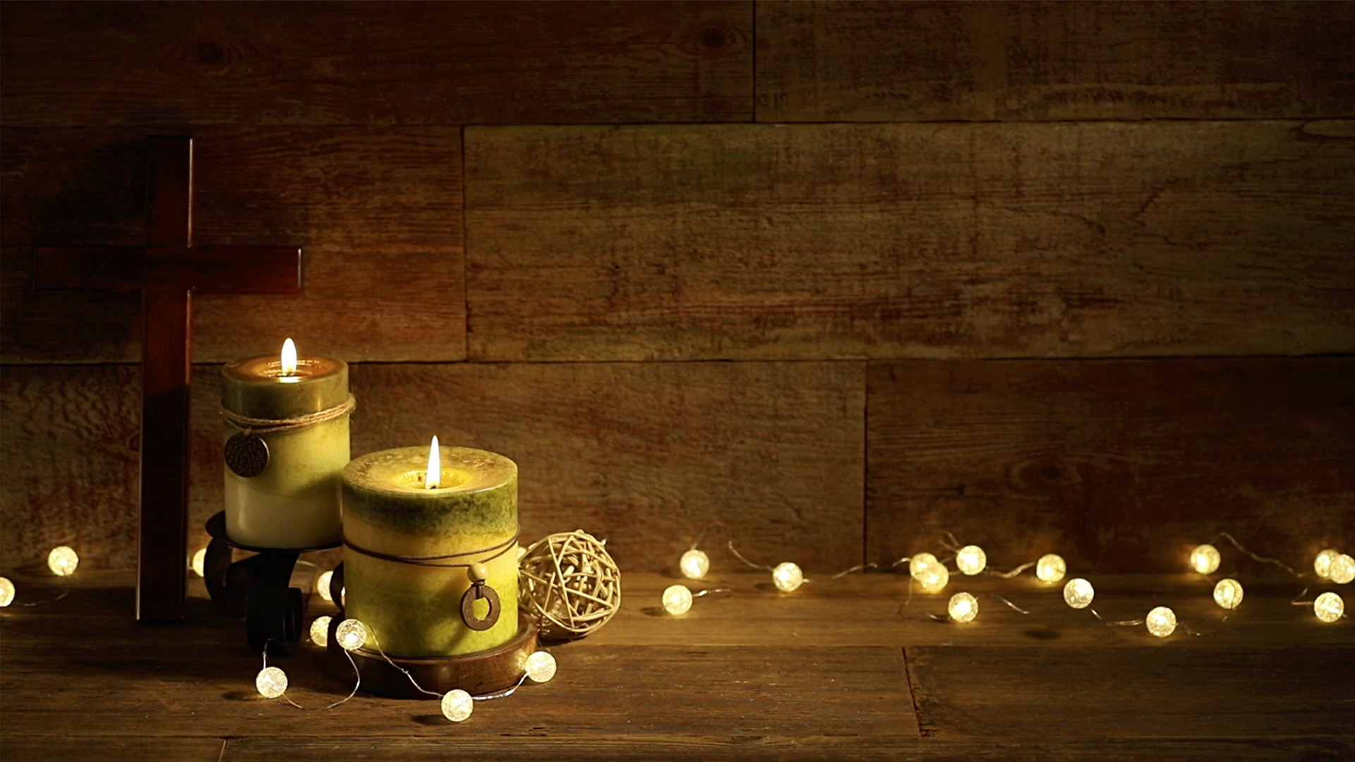 Candles And Cross With Christmas Lights On Wood Background